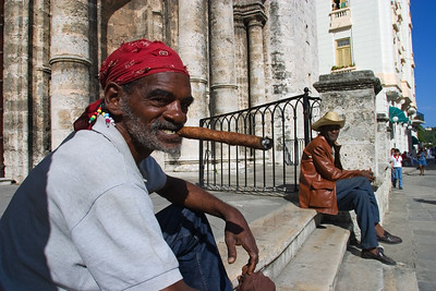 Old man enjoying cigar on the steps of churc in a plaza, Havan, Cuba.