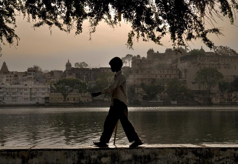 Boy walking on a wall along lake Pichola in Udaipur. <br /> <br /> Rajasthan, India, 2011.