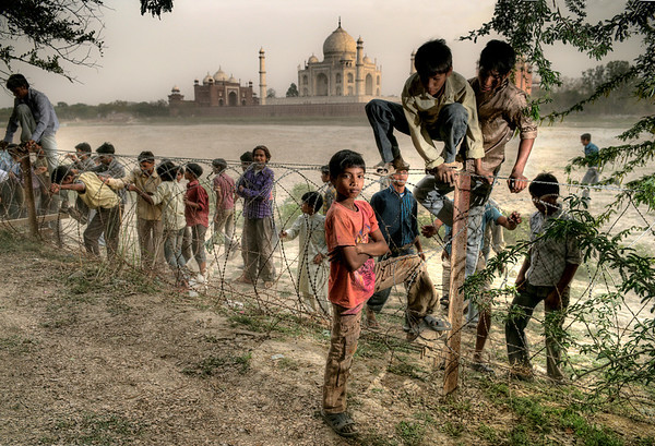 Local boys jump back over the security fence after there cricket match is interrupted by patrolling soldiers.  Taj Mahal, Agra, India, 2011.
