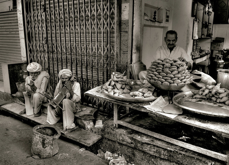 Street musicians playing beside a food stall.<br /> <br /> Jaipur, Rajasthan, India, 2011.