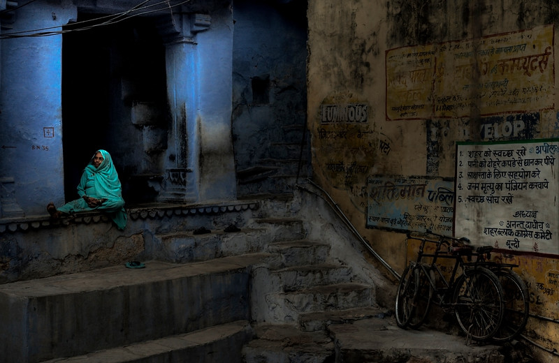 Woman sitting outside her home at dusk in the town of Bundi.<br /> <br /> Rajasthan, India, 2011.