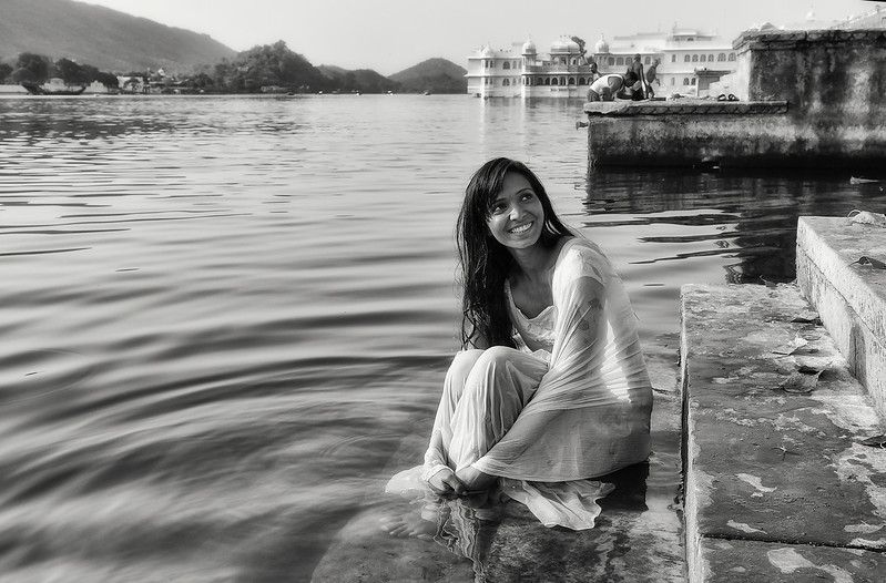 Young woman washing herself in lake Pichola.