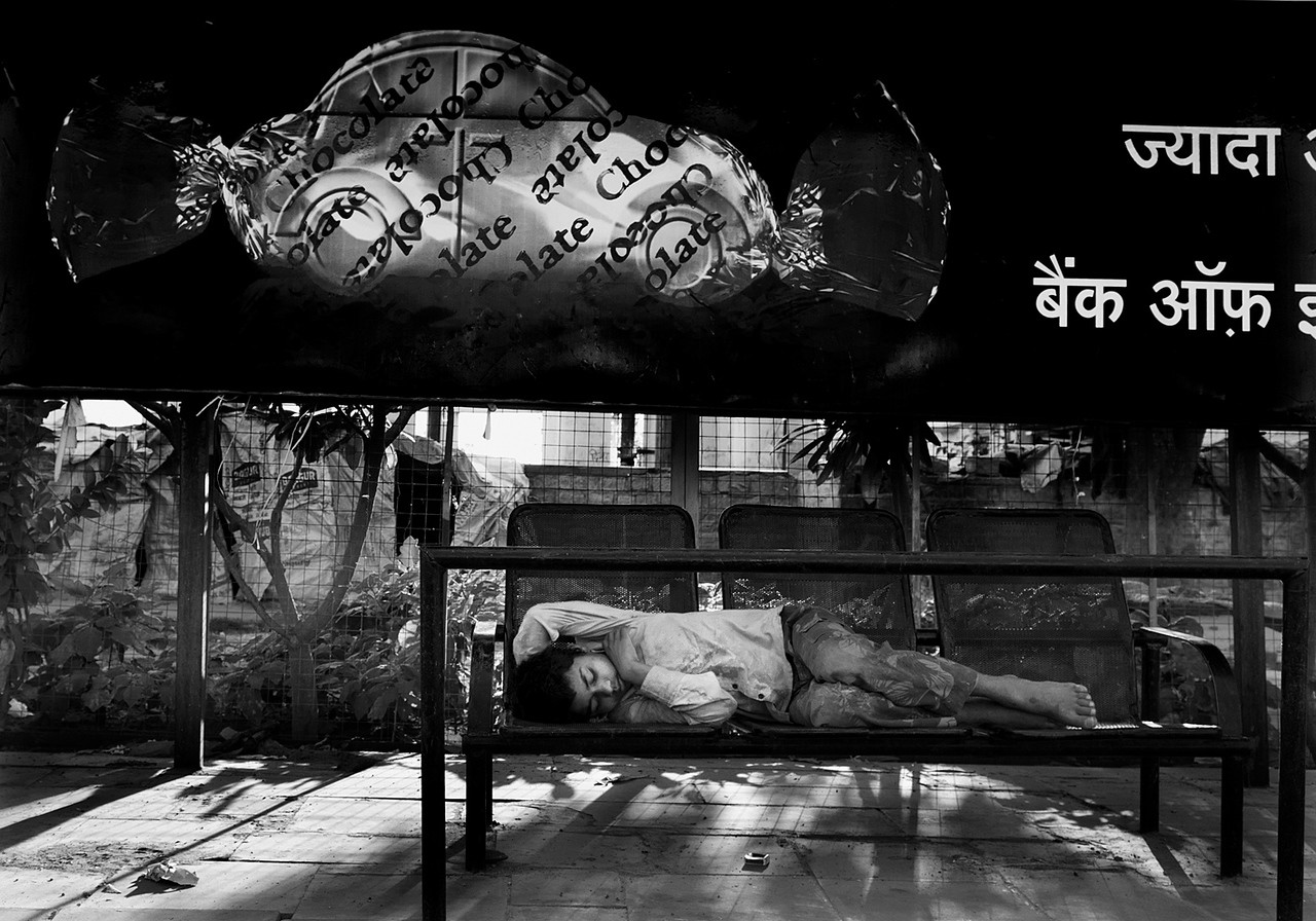 homeless boy sleeping on a bench.<br /> <br /> Delhi, India, 2011.