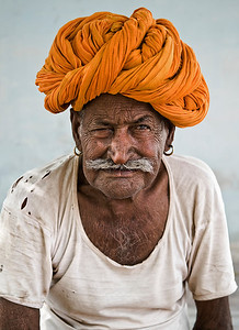 Turbans worn in Rajastan are referred to as the Pagari. They vary in style, colour and size. They also indicate a wearer's social class, caste, region and the occasion it being worn for. Its shape and size may also vary with the climatic conditions of the different regions. Turbans in the hot desert areas are large and loose. Farmers and shepherds, who need constant protection from the elements of nature, wear some of the biggest turbans. The Rajasthani turban also has many practical functions. Exhausted travellers use it as a pillow, a blanket or a towel. It can be used to strain muddy water. An unravelled turban can also be used as a rope to draw water from a well with a bucket  Small farming village outside Bundi, Rajasthan, India, 2011.