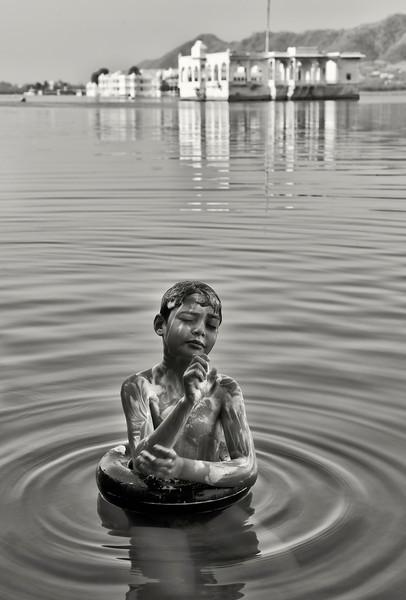 Boy baything in Lake Pichola.<br /> <br /> Udaipur,Rajasthan, India, 2011.