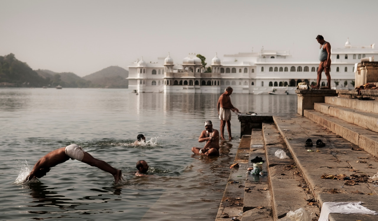 Men bathing in lake Pichola with the lake palace in the background. <br /> <br /> Udaipur, Rajasthan, India, 2011.