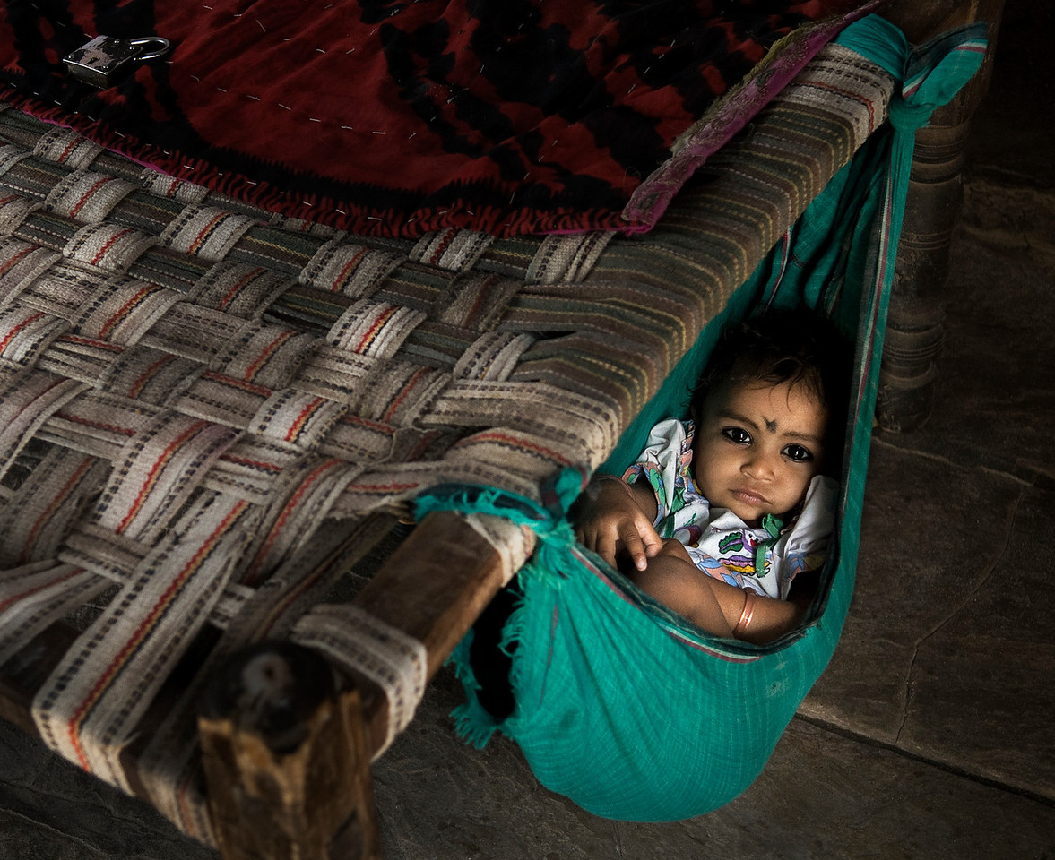 The caretaker at a local school leaves her daughter resting on a hammock whist she gets on with her duties.<br /> <br /> Budi, Rajasthan, India, 2011.