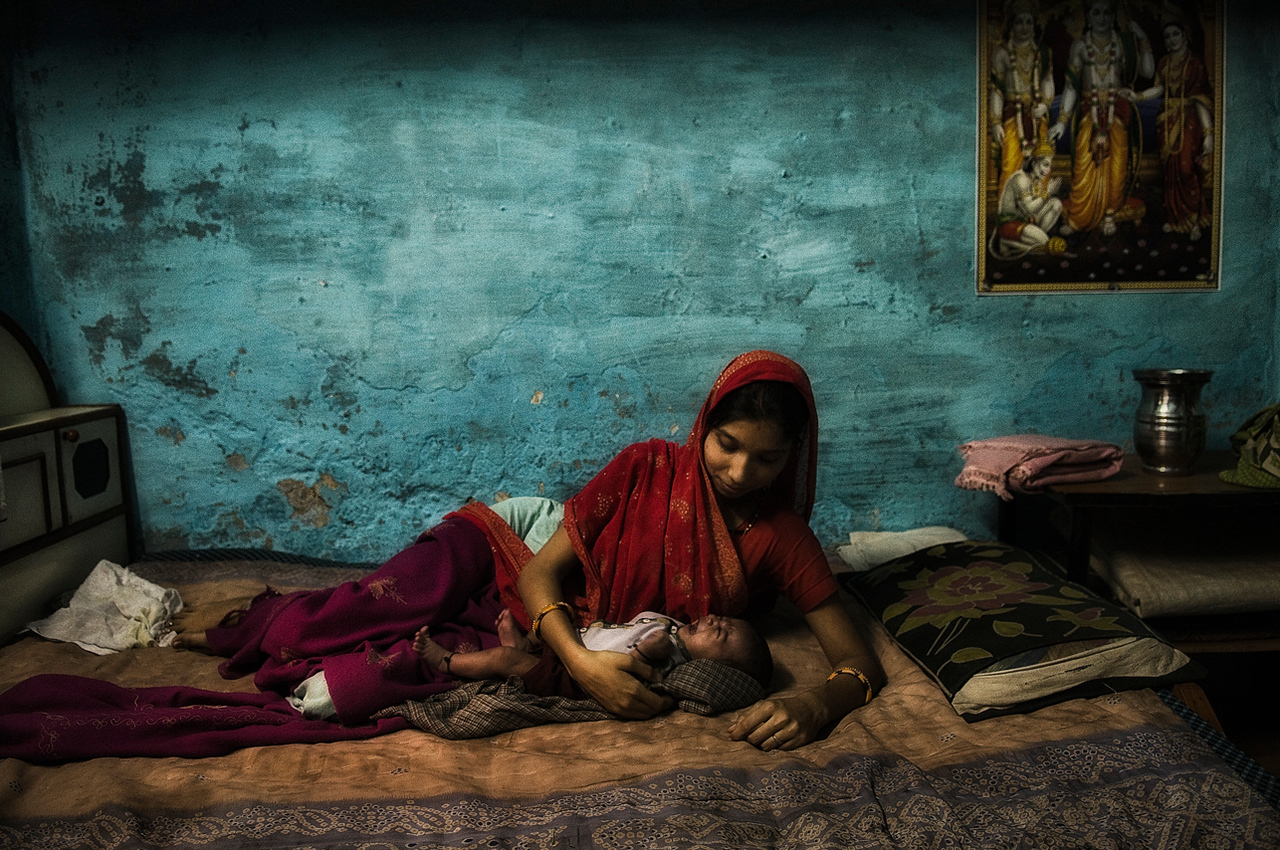 Mother cuddles her newly born baby in her home, in the small town of Bundi<br /> <br /> Rajasthan, 2011.