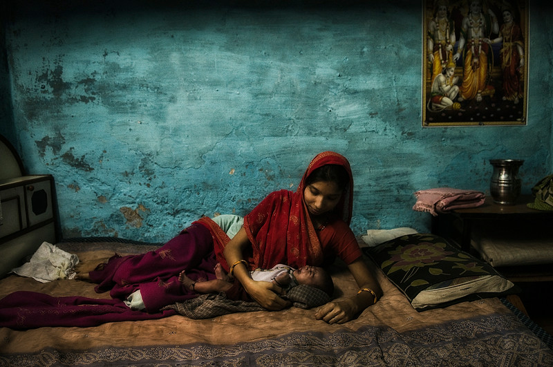 Mother cuddles her newly born baby in her home, in the small town of Bundi  Rajasthan, 2011.