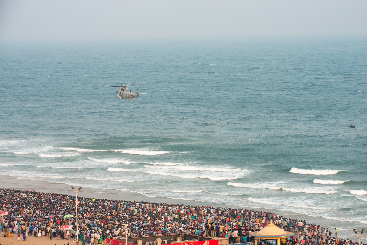Naval helicopter over the crowds on Ramakrishna beach. The Eastern Naval Command, Visakhapatnam celebrated the Navy Day on December 4, marking the day Indian Navy Missile Boats carried out a deadly attack on Karachi Harbour in the 1971 Indo-Pak war.<br /> <br /> Public could view from RK Beach, the manoeuvres by Destroyers, Corvettes, fast attack craft and Landing Ships, beach assault by Marine Commandos, Sky Diving, close range anti-aircraft firing, band performance, formation anchoring, and a host of other exercises. A total of 17 ships, 13 aircraft, and a submarine took part in the grand display and demonstration.  Visakhapatnam (Vizag), Andhra Pradesh, India.