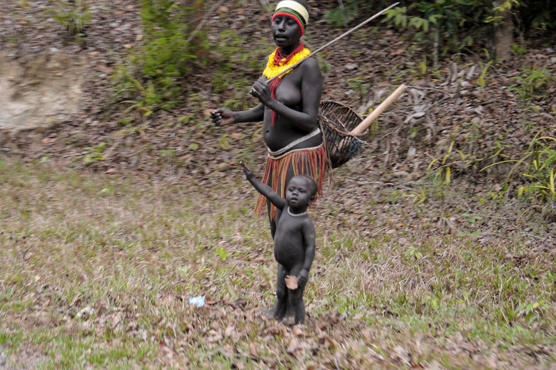 Jarawa tribal women with child wait at the side as they know the timing of the convoy. Jarawa (Jarwa) are one of the adivasi indigenous peoples of the Andaman Islands in India. Their present numbers are estimated at between 250–400 individuals. Some of them come to the Great Andaman Trunk Road (National Highway 223 which connects Port Blair and Diglipur in the Andaman and Nicobar Islands. India.