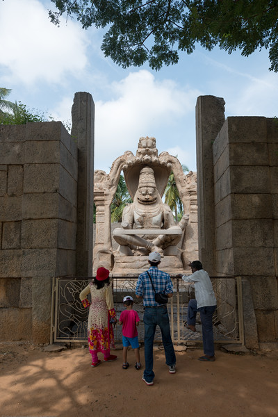 Visitors to the Lakshmi Narasimha. The Lakshmi Narasimha statue is the largest statue in Hampi. Narasimha is sitting on the coil of a giant seven-headed snake called Sesha. The heads of the snake acts as the hood above his head. The god sits in a cross-legged Yoga position with a belt supporting the knees.<br /> <br /> Narasimha (means half-man'half-lion in local the languages) is on of the ten incarnations (avatar) of Lord Vishnu. The original statue contained the image of goddess Lakshmi, consort of the god, sitting on his lap. But this statue has been damaged seriously during the raid leading to the fall of Vijayanagara.