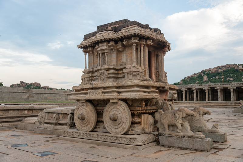 Stone Chariot is built on a rectangular platform of a feet or so high. All around this base platform is carved with mythical battle scenes. Though the chariot is not resting on it, the four giant wheels attached mimic the real life ones complete with the axis shafts & the brakes. A series of concentric floral motifs decorate the wheels.<br /> <br /> Vittala Temple is the most extravagant architectural showpiece of Hampi.  Vittala, after whom the temple is known, is a form of Lord Vishnu. The temple was originally built in the 15th century AD. Hampi, Karnataka is a world famous UNESCO World Heritage Site.