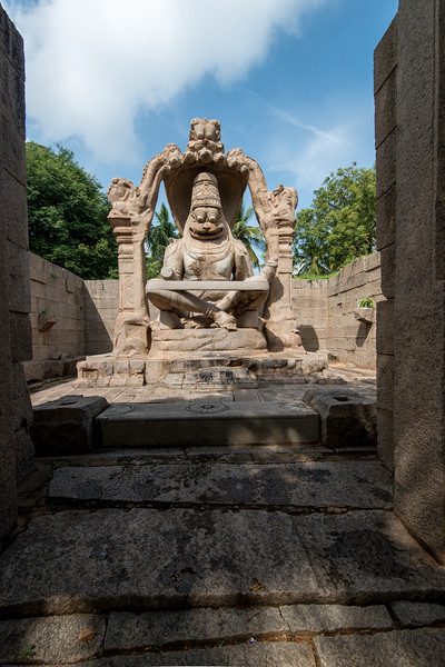 Lakshmi Narasimha statue is the largest statue in Hampi. Narasimha is sitting on the coil of a giant seven-headed snake called Sesha. The heads of the snake acts as the hood above his head. The original statue contained the image of goddess Lakshmi, consort of the god, sitting on his lap. But this statue has been damaged seriously during the raid leading to the fall of Vijayanagara. But the goddess's hand is visible resting on his back in embracing posture.