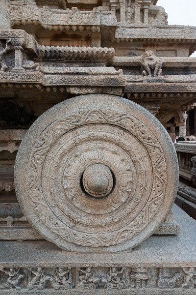 Stone Chariot at Vittala Temple is built on a rectangular platform of a feet or so high. All around this base platform is carved with mythical battle scenes. Though the chariot is not resting on it, the four giant wheels attached mimic the real life ones complete with the axis shafts & the brakes. A series of concentric floral motifs decorate the wheels. It appears from the marks on the platform, where the wheels rest, the wheels were free to move around the axis but are now restrained to prevent damage.<br /> <br /> Hampi, Karnataka is a world famous UNESCO World Heritage Site.