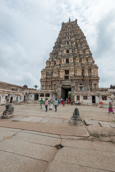Visitors and pilgrims at Virupaksha temple. <br /> Virupaksha temple is the oldest and the principal Shiva Temple in Hampi. <br /> <br /> This pastel painted 9 storied tower with a pair of cow horn like projections on top is the most prominent landmark in Hampi. The lower two tiers of the tower is made of decorated stone work. The most striking feature of this court is the central pillared hall known as the Ranga Mandapa added to the temple complex in 1510 AD by Krishadeva Raya.