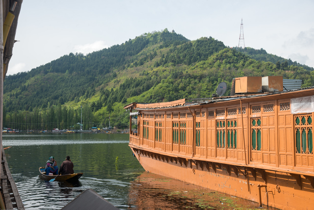 Shikaras ferry on Dal Lake between floating house boats. oDal Lake, Srinagar, Jammu and Kashmir, India.<br /> <br /> They are usually moored at the edges of the Dal Lake and Nageen lakes. Some were built in the early 1900s, and are still being rented out to tourists.