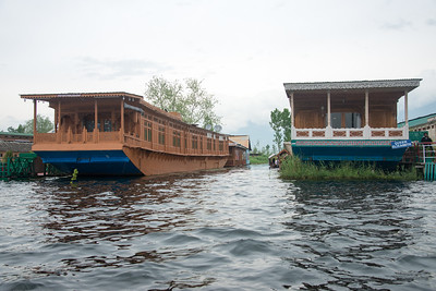 """Floating houseboats on Dal Lake, Jammu and Kashmir, India. The shore line of the lake, is about 15.5 kilometres (9.6 mi), is encompassed by a boulevard lined with Mughal era gardens, parks, houseboats and hotels. The lake covers an area of 18 square kilometres (6.9 sq mi) and is part of a natural wetland which covers 21.1 square kilometres (8.1 sq mi), including its floating gardens. The floating gardens, known as """"Rad"""" in Kashmiri, blossom with lotus flowers during July and August."""