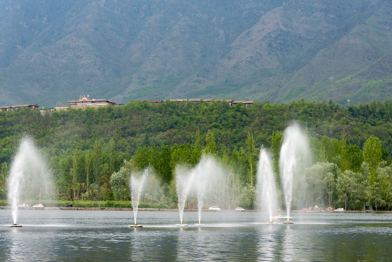 """Water fountains on Dal Lake, Jammu and Kashmir, India. The shore line of the lake, is about 15.5 kilometres (9.6 mi), is encompassed by a boulevard lined with Mughal era gardens, parks, houseboats and hotels. The lake covers an area of 18 square kilometres (6.9 sq mi) and is part of a natural wetland which covers 21.1 square kilometres (8.1 sq mi), including its floating gardens. The floating gardens, known as """"Rad"""" in Kashmiri, blossom with lotus flowers during July and August."""