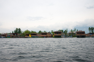 """Row of house boats on Dal Lake, Jammu and Kashmir, India. The shore line of the lake, is about 15.5 kilometres (9.6 mi), is encompassed by a boulevard lined with Mughal era gardens, parks, houseboats and hotels. The lake covers an area of 18 square kilometres (6.9 sq mi) and is part of a natural wetland which covers 21.1 square kilometres (8.1 sq mi), including its floating gardens. The floating gardens, known as """"Rad"""" in Kashmiri, blossom with lotus flowers during July and August."""