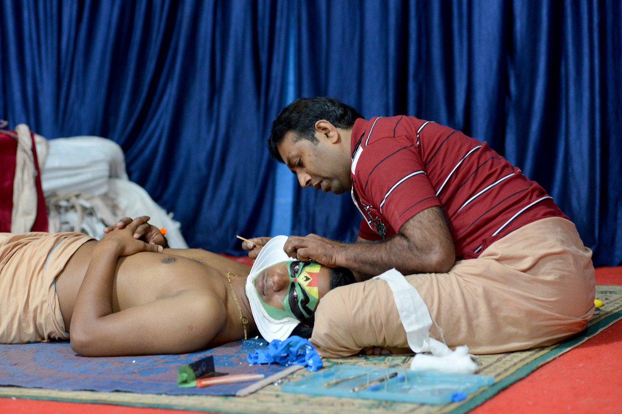 Facial make up being applied onto Lord Indra's handsome son - Jayantha. It can take anywhere from 3 to 4 hours for this.<br /> <br /> On the right is Shri Kalamandalam Shiju Kumar. Born on April 10 in Thachonam a village near Kallara. He learned Kathakali from 1991 to 1997, in Kerala Kalamadalam from Gurus Kalamandalam Rajasekharan, Kalamandalam Prasannakumar and Kalamandalam Gopakumar. In 1997 wrote a new kathakali story EKALAVYACHARITHAM performed in Kalamandalam, and performing so many stages in Kerala.<br /> <br /> Mudra Kathakali Centre, Thekkady. Kathakali, literally meaning `story-play', is a dance-drama originated in the 17th century in Kerala, one of the smallest states in India lying on the west coast of the Indian peninsula. Kathakali is the result of a fusion between all Indian theater tradition represented by Koodiyattom and the indigenous tradition of folk dance forms. It was one of the Rajas (Chieftain) of Kottarakkara, who wrote the first play intended for Kathakali performance. They form a cycle of eight stories based on Ramayana. Stories typically deal with the Mahabharata, Ramayana and the ancient scriptures known as the Puranas. This is performed in a text which is generally Sanskritised Malayalam.<br /> <br /> Thekkady (Idukki district) in Kerala is the location of the Periyar National Park, which is an important tourist attraction in India.