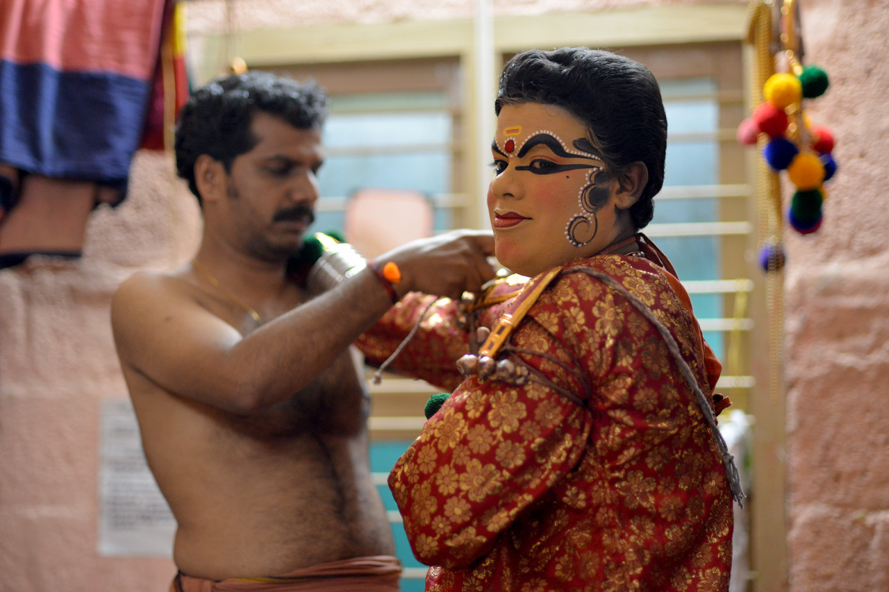 The male performer Kalamandal Subin with help from others dresses up as Lalitha,the demon lady Nakrathundi (Servant of the powerful demon Nakasura).<br /> <br /> Mudra Kathakali Centre, Thekkady. Kathakali, literally meaning `story-play', is a dance-drama originated in the 17th century in Kerala, one of the smallest states in India lying on the west coast of the Indian peninsula. Kathakali is the result of a fusion between all Indian theater tradition represented by Koodiyattom and the indigenous tradition of folk dance forms. It was one of the Rajas (Chieftain) of Kottarakkara, who wrote the first play intended for Kathakali performance. They form a cycle of eight stories based on Ramayana. Stories typically deal with the Mahabharata, Ramayana and the ancient scriptures known as the Puranas. This is performed in a text which is generally Sanskritised Malayalam.<br /> <br /> Thekkady (Idukki district) in Kerala is the location of the Periyar National Park, which is an important tourist attraction in India.