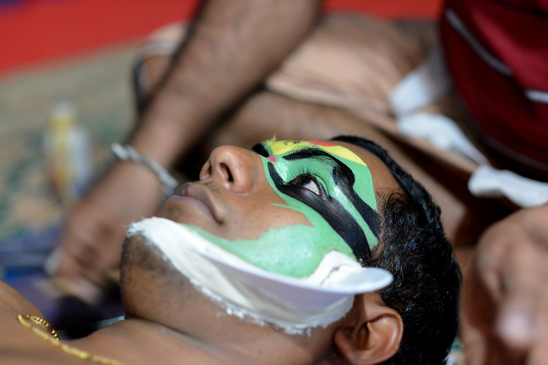 Facial make up being applied onto Lord Indra's handsome son -Jayantha. It can take anywhere from 3 to 4 hours for this.<br /> <br /> Mudra Kathakali Centre, Thekkady. Kathakali, literally meaning `story-play', is a dance-drama originated in the 17th century in Kerala, one of the smallest states in India lying on the west coast of the Indian peninsula. Kathakali is the result of a fusion between all Indian theater tradition represented by Koodiyattom and the indigenous tradition of folk dance forms. It was one of the Rajas (Chieftain) of Kottarakkara, who wrote the first play intended for Kathakali performance. They form a cycle of eight stories based on Ramayana. Stories typically deal with the Mahabharata, Ramayana and the ancient scriptures known as the Puranas. This is performed in a text which is generally Sanskritised Malayalam.<br /> <br /> Thekkady (Idukki district) in Kerala is the location of the Periyar National Park, which is an important tourist attraction in India.