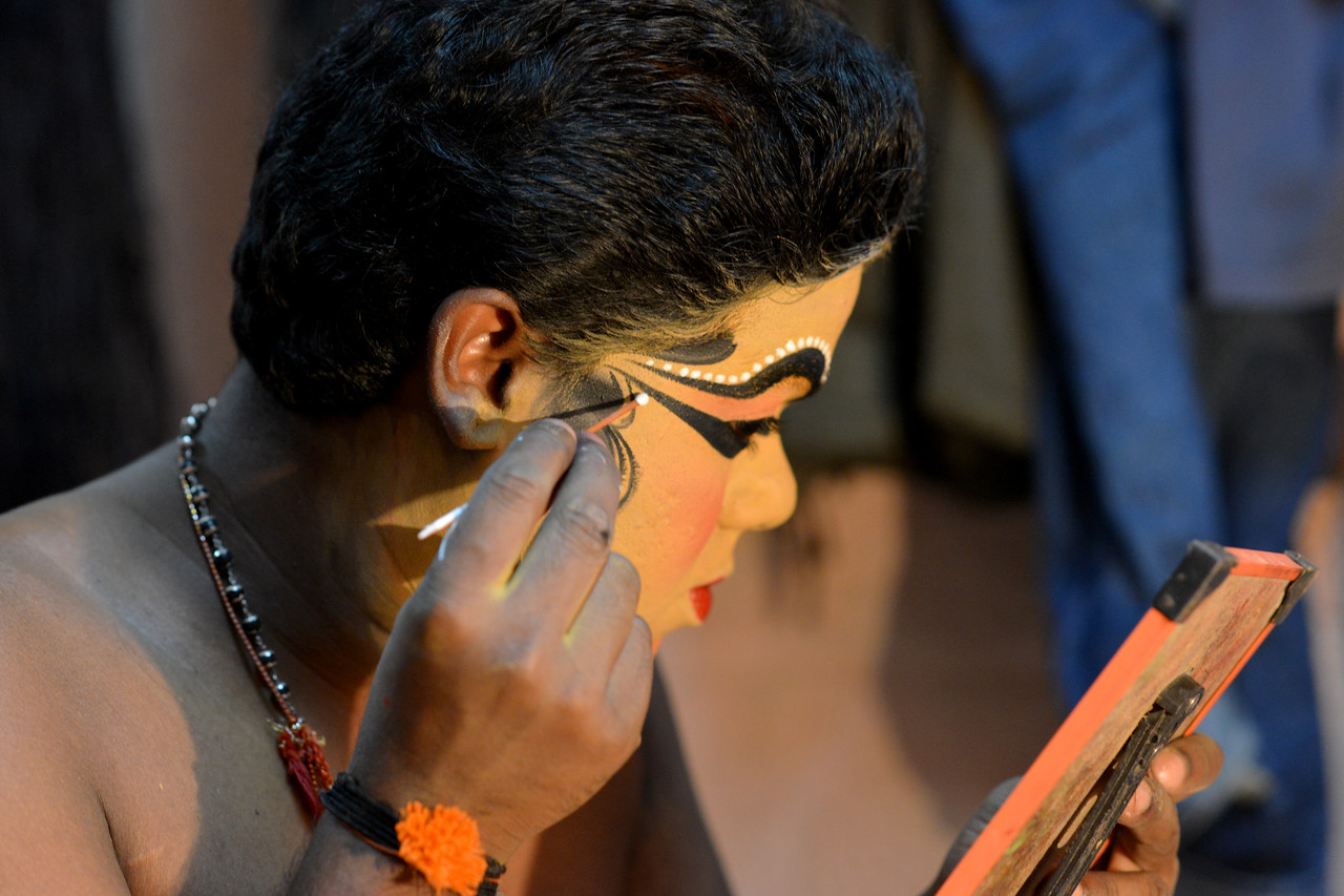 The male actor Kalamandal Subin applies make up to dress up as Lalitha,the demon lady Nakrathundi (Servant of the powerful demon Nakasura). Typically takes 3 to 4 hours to apply this make up.<br /> <br /> Mudra Kathakali Centre, Thekkady. Kathakali, literally meaning `story-play', is a dance-drama originated in the 17th century in Kerala, one of the smallest states in India lying on the west coast of the Indian peninsula. Kathakali is the result of a fusion between all Indian theater tradition represented by Koodiyattom and the indigenous tradition of folk dance forms. It was one of the Rajas (Chieftain) of Kottarakkara, who wrote the first play intended for Kathakali performance. They form a cycle of eight stories based on Ramayana. Stories typically deal with the Mahabharata, Ramayana and the ancient scriptures known as the Puranas. This is performed in a text which is generally Sanskritised Malayalam.<br /> <br /> Thekkady (Idukki district) in Kerala is the location of the Periyar National Park, which is an important tourist attraction in India.