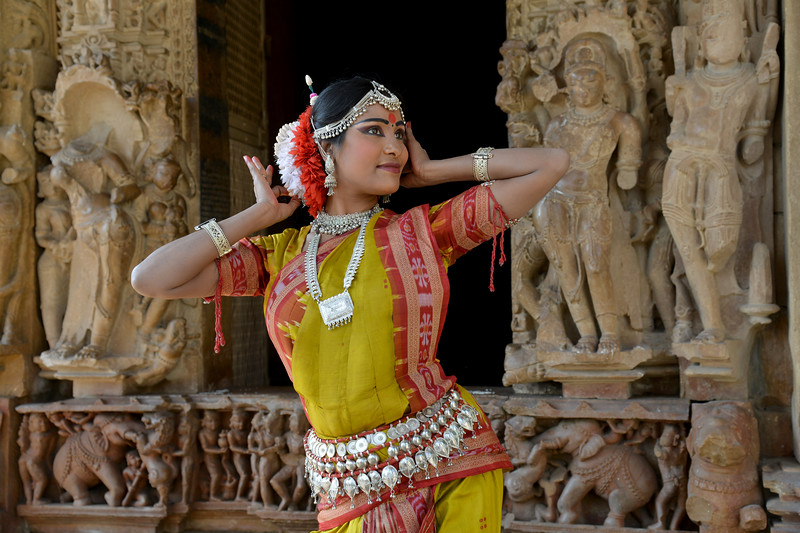 "Odissi dancer Bithika Mistry strikes a dance pose at the Khajuraho Temple.<br /> <br /> <br /> Khajuraho - Land Of The Moon God is located in the Indian state of Madhya Pradesh (MP) and roughly 620 kilometers (385 miles) southeast of New Delhi. Khajuraho was the cultural capital of the Chandela Rajputs, a Hindu dynasty that ruled from the 10th to 12th centuries. The temples of Khajuraho are famous for their so-called ""erotic sculptures"".<br /> <br /> Symbolising a medieval legacy, the Khajuraho temples are a perfect fusion of architectural and sculptural excellence, representing one of the finest examples of Indian art. To some, they are the most graphic, erotic and sensuous sculptures the world has ever known. But Khajuraho has not received the attention it deserves for its significant contribution to the religious art of India - there are literally hundreds of exquisite images on the interior and exterior walls of the shrines.<br /> <br /> Architecturally they are unique. While each temple has a distinct plan and design, several features are common to all. They are all built on high platforms, several metres off the ground. The stone used throughout is either granite or a combination of light sandstone and granite. Each of these temples has an entrance hall or mandapa, and a sanctum sanctorum or garbha griha. The roofs of these various sections have a distinct form. The porch and hall have pyramidal roofs made of several horizontal layers. The inner sanctum's roof is a conical tower - a colossal pile of stone (often 30m high) made of an arrangement of miniature towers called shikharas."