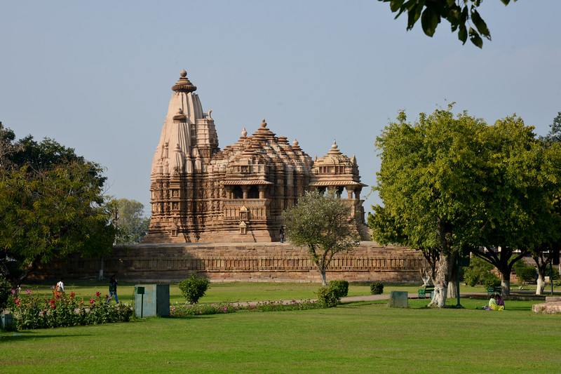 "Khajuraho Temple Complex. Khajuraho - Land Of The Moon God is located in the Indian state of Madhya Pradesh (MP) and roughly 620 kilometers (385 miles) southeast of New Delhi. Khajuraho was the cultural capital of the Chandela Rajputs, a Hindu dynasty that ruled from the 10th to 12th centuries. The temples of Khajuraho are famous for their so-called ""erotic sculptures"".<br /> <br /> Symbolising a medieval legacy, the Khajuraho temples are a perfect fusion of architectural and sculptural excellence, representing one of the finest examples of Indian art. To some, they are the most graphic, erotic and sensuous sculptures the world has ever known. But Khajuraho has not received the attention it deserves for its significant contribution to the religious art of India - there are literally hundreds of exquisite images on the interior and exterior walls of the shrines.<br /> <br /> Architecturally they are unique. While each temple has a distinct plan and design, several features are common to all. They are all built on high platforms, several metres off the ground. The stone used throughout is either granite or a combination of light sandstone and granite. Each of these temples has an entrance hall or mandapa, and a sanctum sanctorum or garbha griha. The roofs of these various sections have a distinct form. The porch and hall have pyramidal roofs made of several horizontal layers. The inner sanctum's roof is a conical tower - a colossal pile of stone (often 30m high) made of an arrangement of miniature towers called shikharas."