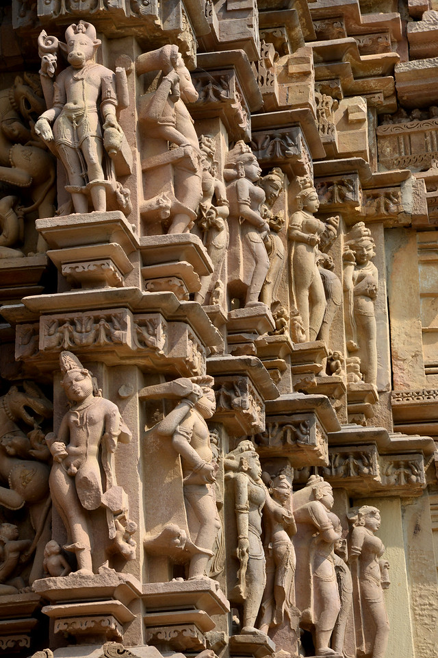 "Detailed carvings on the temple walls. Khajuraho - Land Of The Moon God is located in the Indian state of Madhya Pradesh (MP) and roughly 620 kilometers (385 miles) southeast of New Delhi. Khajuraho was the cultural capital of the Chandela Rajputs, a Hindu dynasty that ruled from the 10th to 12th centuries. The temples of Khajuraho are famous for their so-called ""erotic sculptures"".<br /> <br /> Symbolising a medieval legacy, the Khajuraho temples are a perfect fusion of architectural and sculptural excellence, representing one of the finest examples of Indian art. To some, they are the most graphic, erotic and sensuous sculptures the world has ever known. But Khajuraho has not received the attention it deserves for its significant contribution to the religious art of India - there are literally hundreds of exquisite images on the interior and exterior walls of the shrines.<br /> <br /> Architecturally they are unique. While each temple has a distinct plan and design, several features are common to all. They are all built on high platforms, several metres off the ground. The stone used throughout is either granite or a combination of light sandstone and granite. Each of these temples has an entrance hall or mandapa, and a sanctum sanctorum or garbha griha. The roofs of these various sections have a distinct form. The porch and hall have pyramidal roofs made of several horizontal layers. The inner sanctum's roof is a conical tower - a colossal pile of stone (often 30m high) made of an arrangement of miniature towers called shikharas."