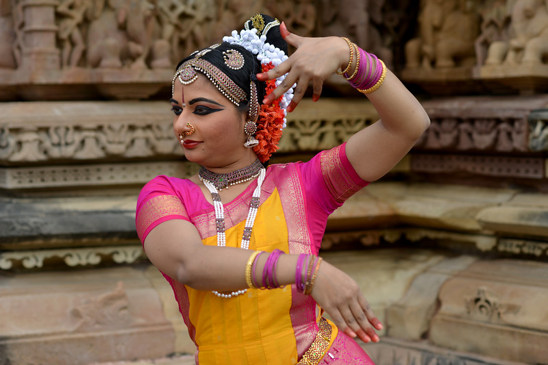 """Kuchipudi dancer Abhinaya Nagajothy striking a dance pose at the Khajuraho Temple. <br /> Khajuraho - Land Of The Moon God is located in the Indian state of Madhya Pradesh (MP) and roughly 620 kilometers (385 miles) southeast of New Delhi. Khajuraho was the cultural capital of the Chandela Rajputs, a Hindu dynasty that ruled from the 10th to 12th centuries. The temples of Khajuraho are famous for their so-called """"erotic sculptures"""".<br /> <br /> Symbolising a medieval legacy, the Khajuraho temples are a perfect fusion of architectural and sculptural excellence, representing one of the finest examples of Indian art. To some, they are the most graphic, erotic and sensuous sculptures the world has ever known. But Khajuraho has not received the attention it deserves for its significant contribution to the religious art of India - there are literally hundreds of exquisite images on the interior and exterior walls of the shrines.<br /> <br /> Architecturally they are unique. While each temple has a distinct plan and design, several features are common to all. They are all built on high platforms, several metres off the ground. The stone used throughout is either granite or a combination of light sandstone and granite. Each of these temples has an entrance hall or mandapa, and a sanctum sanctorum or garbha griha. The roofs of these various sections have a distinct form. The porch and hall have pyramidal roofs made of several horizontal layers. The inner sanctum's roof is a conical tower - a colossal pile of stone (often 30m high) made of an arrangement of miniature towers called shikharas."""