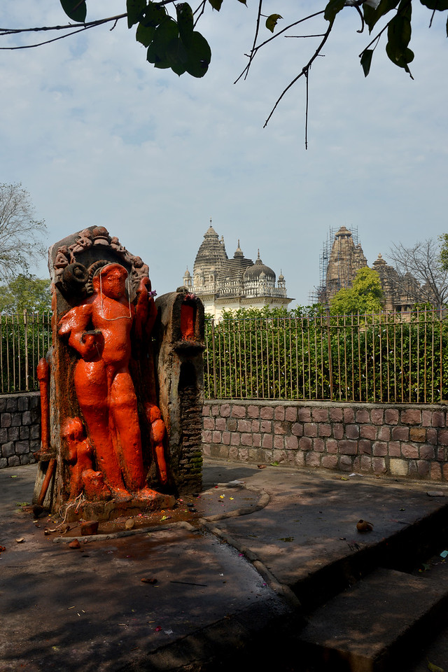 """Hanuman statue at Khajuraho. Khajuraho was the cultural capital of the Chandela Rajputs, a Hindu dynasty that ruled from the 10th to 12th centuries. The temples of Khajuraho are famous for their so-called """"erotic sculptures"""".<br /> <br /> Symbolising a medieval legacy, the Khajuraho temples are a perfect fusion of architectural and sculptural excellence, representing one of the finest examples of Indian art. To some, they are the most graphic, erotic and sensuous sculptures the world has ever known. But Khajuraho has not received the attention it deserves for its significant contribution to the religious art of India - there are literally hundreds of exquisite images on the interior and exterior walls of the shrines.<br /> <br /> Architecturally they are unique. While each temple has a distinct plan and design, several features are common to all. They are all built on high platforms, several metres off the ground. The stone used throughout is either granite or a combination of light sandstone and granite. Each of these temples has an entrance hall or mandapa, and a sanctum sanctorum or garbha griha. The roofs of these various sections have a distinct form. The porch and hall have pyramidal roofs made of several horizontal layers. The inner sanctum's roof is a conical tower - a colossal pile of stone (often 30m high) made of an arrangement of miniature towers called shikharas."""