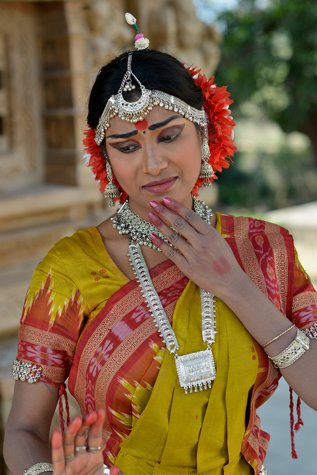 """Odissi dancer Bithika Mistry displaying various mudras at the Khajuraho Temple.<br /> <br /> <br /> Khajuraho - Land Of The Moon God is located in the Indian state of Madhya Pradesh (MP) and roughly 620 kilometers (385 miles) southeast of New Delhi. Khajuraho was the cultural capital of the Chandela Rajputs, a Hindu dynasty that ruled from the 10th to 12th centuries. The temples of Khajuraho are famous for their so-called """"erotic sculptures"""".<br /> <br /> Symbolising a medieval legacy, the Khajuraho temples are a perfect fusion of architectural and sculptural excellence, representing one of the finest examples of Indian art. To some, they are the most graphic, erotic and sensuous sculptures the world has ever known. But Khajuraho has not received the attention it deserves for its significant contribution to the religious art of India - there are literally hundreds of exquisite images on the interior and exterior walls of the shrines.<br /> <br /> Architecturally they are unique. While each temple has a distinct plan and design, several features are common to all. They are all built on high platforms, several metres off the ground. The stone used throughout is either granite or a combination of light sandstone and granite. Each of these temples has an entrance hall or mandapa, and a sanctum sanctorum or garbha griha. The roofs of these various sections have a distinct form. The porch and hall have pyramidal roofs made of several horizontal layers. The inner sanctum's roof is a conical tower - a colossal pile of stone (often 30m high) made of an arrangement of miniature towers called shikharas."""