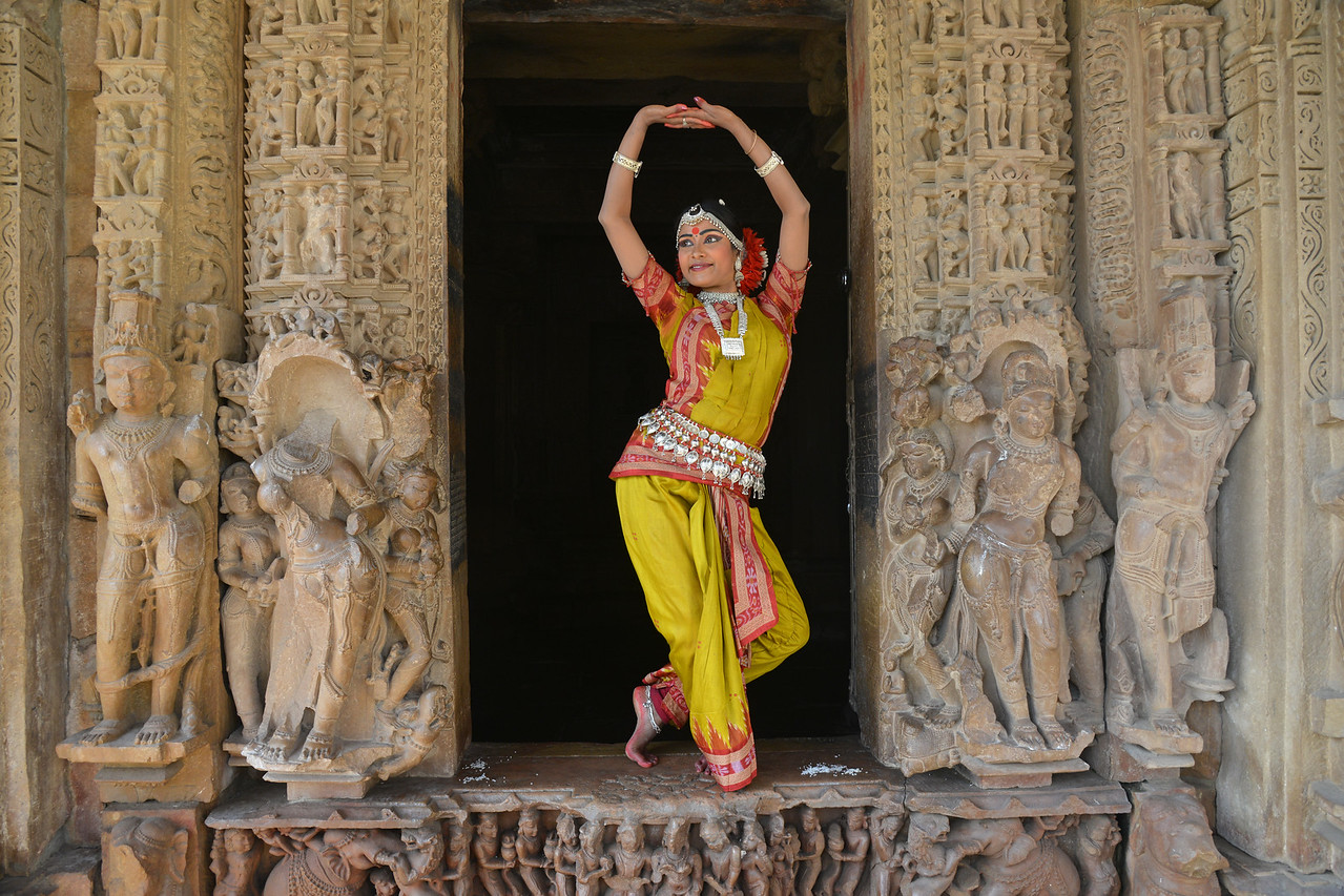 """Odissi dancer Bithika Mistry in a Odissi dance pose at the Khajuraho Temple.<br /> <br /> <br /> Khajuraho - Land Of The Moon God is located in the Indian state of Madhya Pradesh (MP) and roughly 620 kilometers (385 miles) southeast of New Delhi. Khajuraho was the cultural capital of the Chandela Rajputs, a Hindu dynasty that ruled from the 10th to 12th centuries. The temples of Khajuraho are famous for their so-called """"erotic sculptures"""".<br /> <br /> Symbolising a medieval legacy, the Khajuraho temples are a perfect fusion of architectural and sculptural excellence, representing one of the finest examples of Indian art. To some, they are the most graphic, erotic and sensuous sculptures the world has ever known. But Khajuraho has not received the attention it deserves for its significant contribution to the religious art of India - there are literally hundreds of exquisite images on the interior and exterior walls of the shrines.<br /> <br /> Architecturally they are unique. While each temple has a distinct plan and design, several features are common to all. They are all built on high platforms, several metres off the ground. The stone used throughout is either granite or a combination of light sandstone and granite. Each of these temples has an entrance hall or mandapa, and a sanctum sanctorum or garbha griha. The roofs of these various sections have a distinct form. The porch and hall have pyramidal roofs made of several horizontal layers. The inner sanctum's roof is a conical tower - a colossal pile of stone (often 30m high) made of an arrangement of miniature towers called shikharas."""