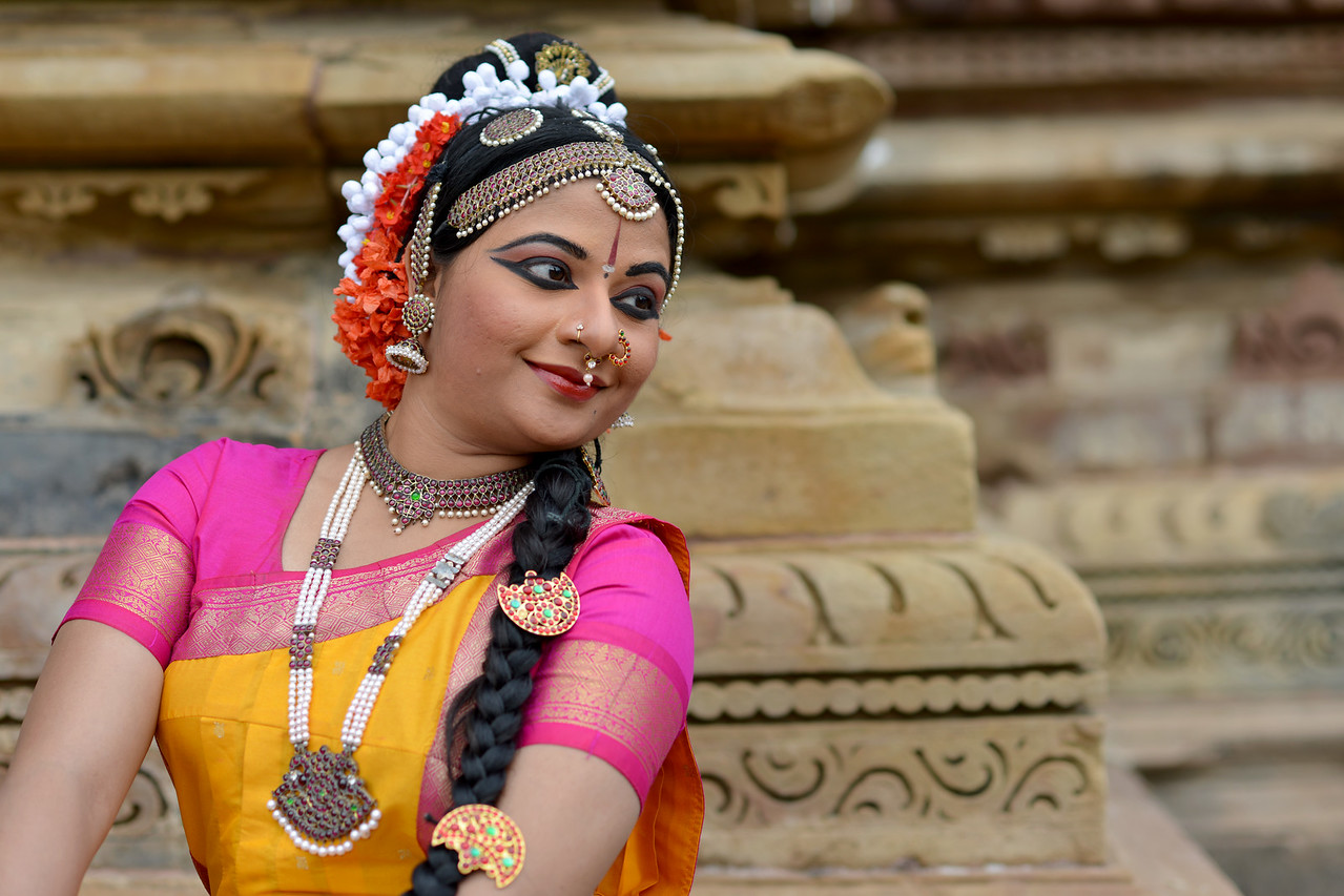 "Kuchipudi dancer Abhinaya Nagajothy at the Khajuraho Temple. <br /> Khajuraho - Land Of The Moon God is located in the Indian state of Madhya Pradesh (MP) and roughly 620 kilometers (385 miles) southeast of New Delhi. Khajuraho was the cultural capital of the Chandela Rajputs, a Hindu dynasty that ruled from the 10th to 12th centuries. The temples of Khajuraho are famous for their so-called ""erotic sculptures"".<br /> <br /> Symbolising a medieval legacy, the Khajuraho temples are a perfect fusion of architectural and sculptural excellence, representing one of the finest examples of Indian art. To some, they are the most graphic, erotic and sensuous sculptures the world has ever known. But Khajuraho has not received the attention it deserves for its significant contribution to the religious art of India - there are literally hundreds of exquisite images on the interior and exterior walls of the shrines.<br /> <br /> Architecturally they are unique. While each temple has a distinct plan and design, several features are common to all. They are all built on high platforms, several metres off the ground. The stone used throughout is either granite or a combination of light sandstone and granite. Each of these temples has an entrance hall or mandapa, and a sanctum sanctorum or garbha griha. The roofs of these various sections have a distinct form. The porch and hall have pyramidal roofs made of several horizontal layers. The inner sanctum's roof is a conical tower - a colossal pile of stone (often 30m high) made of an arrangement of miniature towers called shikharas."