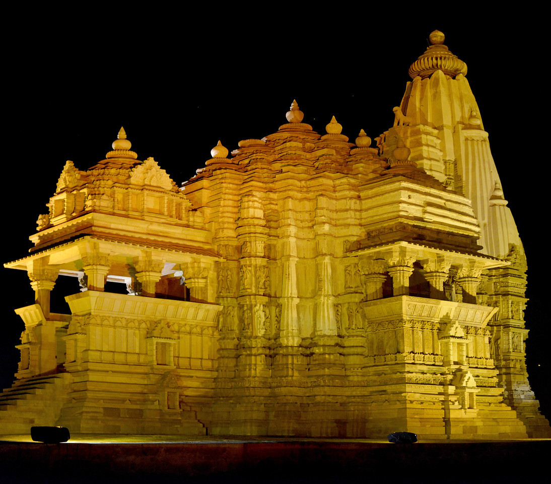 "Night view of Khajuraho Temple. Khajuraho - Land Of The Moon God is located in the Indian state of Madhya Pradesh (MP) and roughly 620 kilometers (385 miles) southeast of New Delhi. Khajuraho was the cultural capital of the Chandela Rajputs, a Hindu dynasty that ruled from the 10th to 12th centuries. The temples of Khajuraho are famous for their so-called ""erotic sculptures"".<br /> <br /> Symbolising a medieval legacy, the Khajuraho temples are a perfect fusion of architectural and sculptural excellence, representing one of the finest examples of Indian art. To some, they are the most graphic, erotic and sensuous sculptures the world has ever known. But Khajuraho has not received the attention it deserves for its significant contribution to the religious art of India - there are literally hundreds of exquisite images on the interior and exterior walls of the shrines.<br /> <br /> Architecturally they are unique. While each temple has a distinct plan and design, several features are common to all. They are all built on high platforms, several metres off the ground. The stone used throughout is either granite or a combination of light sandstone and granite. Each of these temples has an entrance hall or mandapa, and a sanctum sanctorum or garbha griha. The roofs of these various sections have a distinct form. The porch and hall have pyramidal roofs made of several horizontal layers. The inner sanctum's roof is a conical tower - a colossal pile of stone (often 30m high) made of an arrangement of miniature towers called shikharas."