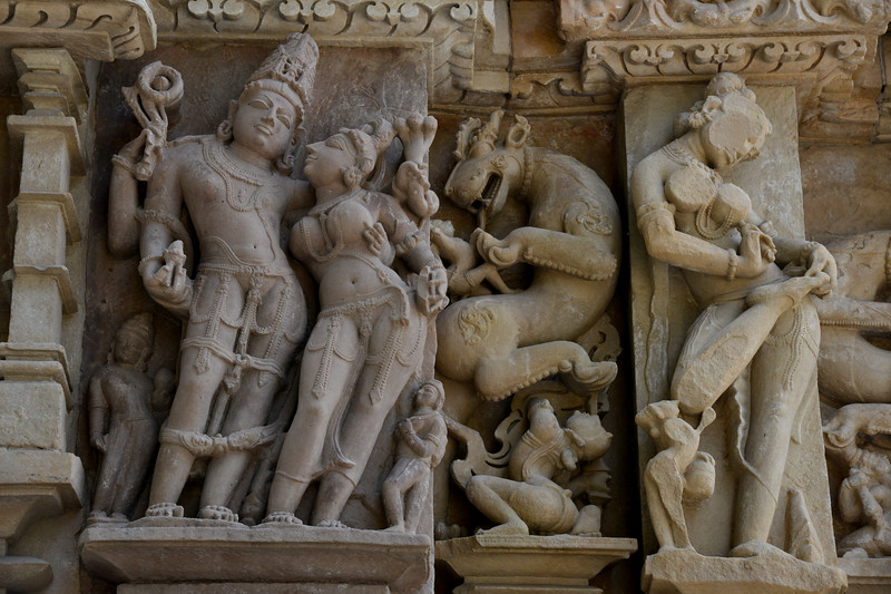 "Close up details of the temple carvings. Khajuraho - Land Of The Moon God is located in the Indian state of Madhya Pradesh (MP) and roughly 620 kilometers (385 miles) southeast of New Delhi. Khajuraho was the cultural capital of the Chandela Rajputs, a Hindu dynasty that ruled from the 10th to 12th centuries. The temples of Khajuraho are famous for their so-called ""erotic sculptures"".<br /> <br /> Symbolising a medieval legacy, the Khajuraho temples are a perfect fusion of architectural and sculptural excellence, representing one of the finest examples of Indian art. To some, they are the most graphic, erotic and sensuous sculptures the world has ever known. But Khajuraho has not received the attention it deserves for its significant contribution to the religious art of India - there are literally hundreds of exquisite images on the interior and exterior walls of the shrines.<br /> <br /> Architecturally they are unique. While each temple has a distinct plan and design, several features are common to all. They are all built on high platforms, several metres off the ground. The stone used throughout is either granite or a combination of light sandstone and granite. Each of these temples has an entrance hall or mandapa, and a sanctum sanctorum or garbha griha. The roofs of these various sections have a distinct form. The porch and hall have pyramidal roofs made of several horizontal layers. The inner sanctum's roof is a conical tower - a colossal pile of stone (often 30m high) made of an arrangement of miniature towers called shikharas."
