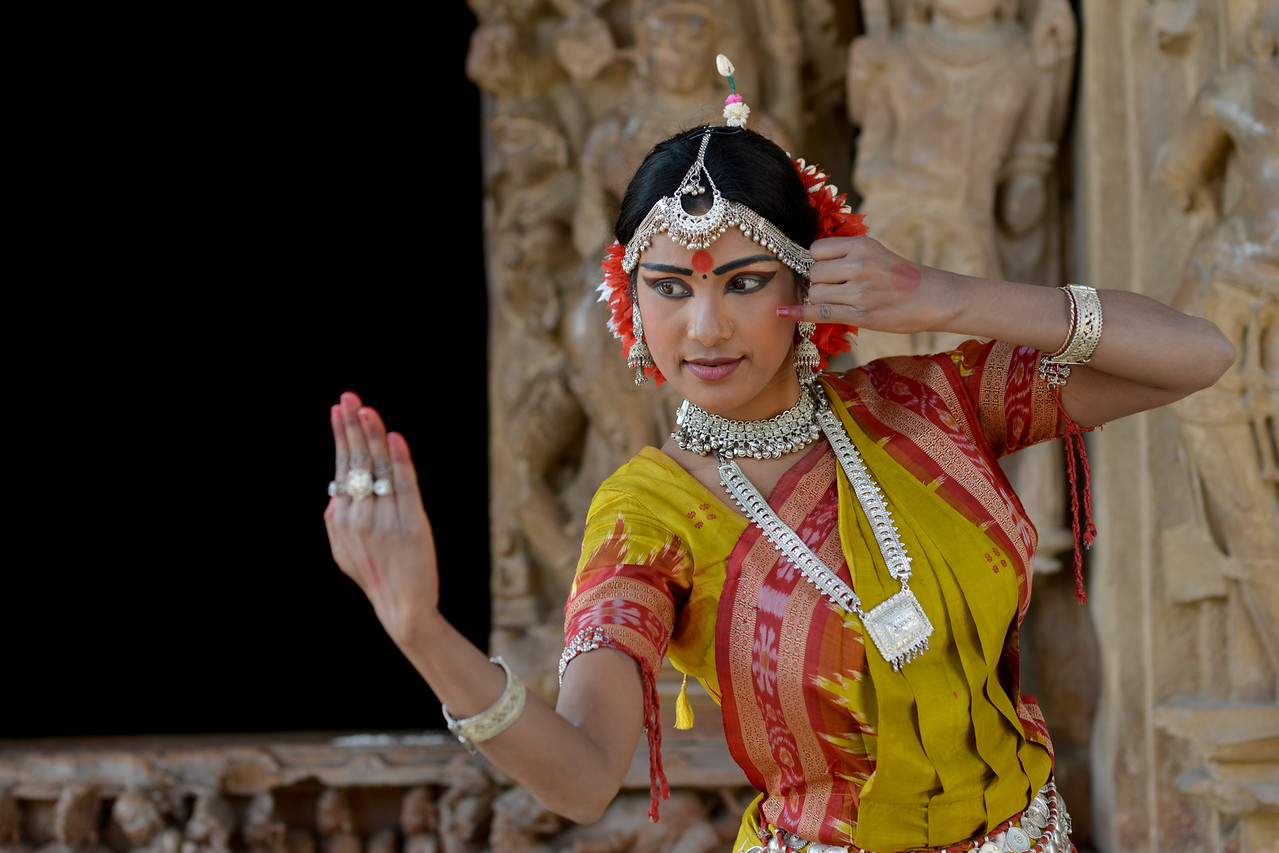 """Odissi dancer Bithika Mistry at the Khajuraho Temple strikes a dance pose.<br /> <br /> Khajuraho - Land Of The Moon God is located in the Indian state of Madhya Pradesh (MP) and roughly 620 kilometers (385 miles) southeast of New Delhi. Khajuraho was the cultural capital of the Chandela Rajputs, a Hindu dynasty that ruled from the 10th to 12th centuries. The temples of Khajuraho are famous for their so-called """"erotic sculptures"""".<br /> <br /> Symbolising a medieval legacy, the Khajuraho temples are a perfect fusion of architectural and sculptural excellence, representing one of the finest examples of Indian art. To some, they are the most graphic, erotic and sensuous sculptures the world has ever known. But Khajuraho has not received the attention it deserves for its significant contribution to the religious art of India - there are literally hundreds of exquisite images on the interior and exterior walls of the shrines.<br /> <br /> Architecturally they are unique. While each temple has a distinct plan and design, several features are common to all. They are all built on high platforms, several metres off the ground. The stone used throughout is either granite or a combination of light sandstone and granite. Each of these temples has an entrance hall or mandapa, and a sanctum sanctorum or garbha griha. The roofs of these various sections have a distinct form. The porch and hall have pyramidal roofs made of several horizontal layers. The inner sanctum's roof is a conical tower - a colossal pile of stone (often 30m high) made of an arrangement of miniature towers called shikharas."""