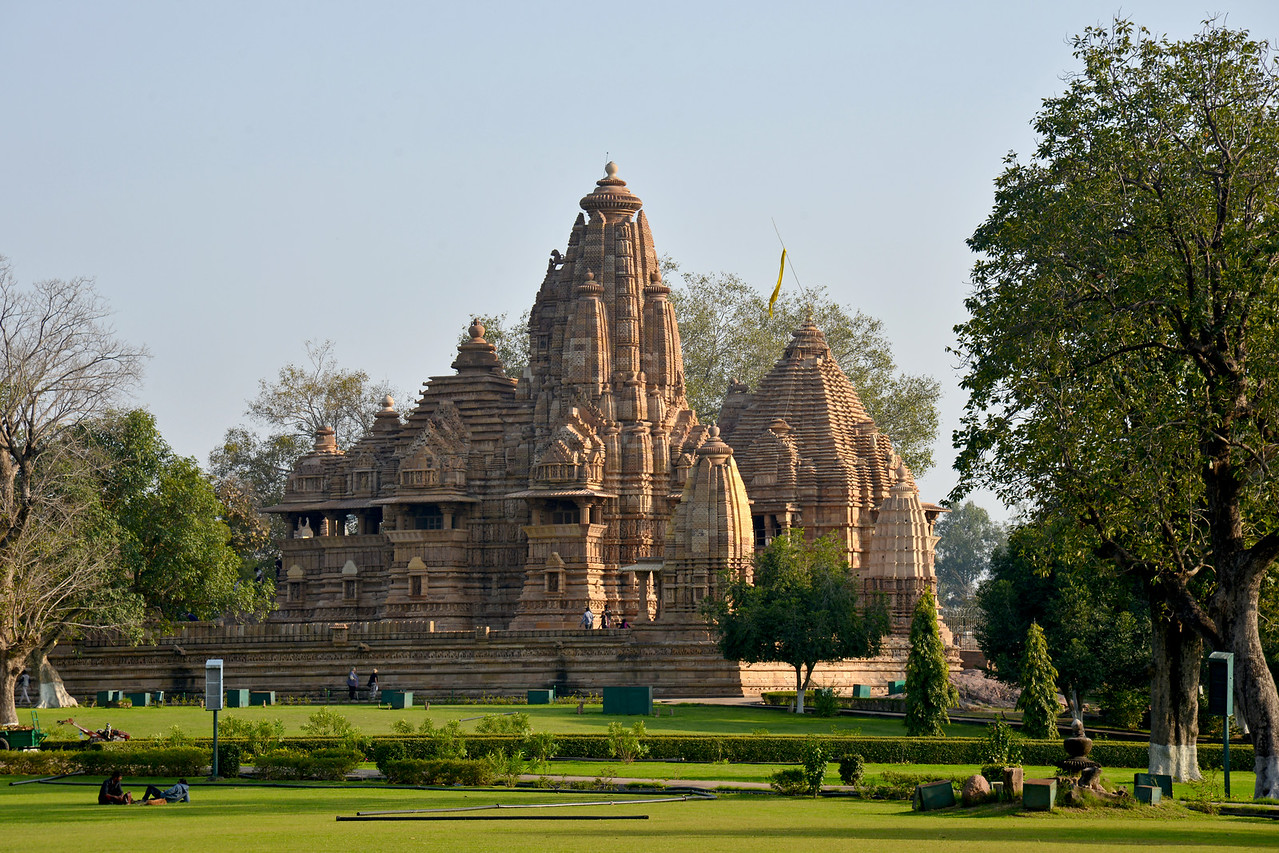 """Temple complex of Khajuraho. Khajuraho - Land Of The Moon God is located in the Indian state of Madhya Pradesh (MP) and roughly 620 kilometers (385 miles) southeast of New Delhi. Khajuraho was the cultural capital of the Chandela Rajputs, a Hindu dynasty that ruled from the 10th to 12th centuries. The temples of Khajuraho are famous for their so-called """"erotic sculptures"""".<br /> <br /> Symbolising a medieval legacy, the Khajuraho temples are a perfect fusion of architectural and sculptural excellence, representing one of the finest examples of Indian art. To some, they are the most graphic, erotic and sensuous sculptures the world has ever known. But Khajuraho has not received the attention it deserves for its significant contribution to the religious art of India - there are literally hundreds of exquisite images on the interior and exterior walls of the shrines.<br /> <br /> Architecturally they are unique. While each temple has a distinct plan and design, several features are common to all. They are all built on high platforms, several metres off the ground. The stone used throughout is either granite or a combination of light sandstone and granite. Each of these temples has an entrance hall or mandapa, and a sanctum sanctorum or garbha griha. The roofs of these various sections have a distinct form. The porch and hall have pyramidal roofs made of several horizontal layers. The inner sanctum's roof is a conical tower - a colossal pile of stone (often 30m high) made of an arrangement of miniature towers called shikharas."""