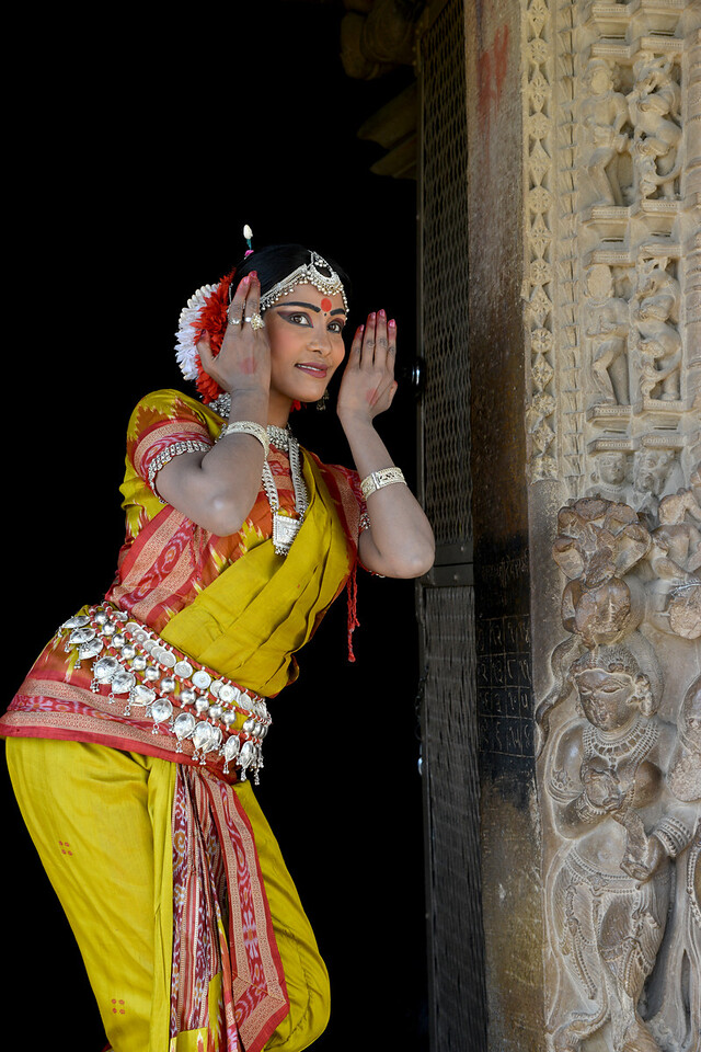 """Odissi dancer Bithika Mistry at the Khajuraho Temple.<br /> <br /> <br /> Khajuraho - Land Of The Moon God is located in the Indian state of Madhya Pradesh (MP) and roughly 620 kilometers (385 miles) southeast of New Delhi. Khajuraho was the cultural capital of the Chandela Rajputs, a Hindu dynasty that ruled from the 10th to 12th centuries. The temples of Khajuraho are famous for their so-called """"erotic sculptures"""".<br /> <br /> Symbolising a medieval legacy, the Khajuraho temples are a perfect fusion of architectural and sculptural excellence, representing one of the finest examples of Indian art. To some, they are the most graphic, erotic and sensuous sculptures the world has ever known. But Khajuraho has not received the attention it deserves for its significant contribution to the religious art of India - there are literally hundreds of exquisite images on the interior and exterior walls of the shrines.<br /> <br /> Architecturally they are unique. While each temple has a distinct plan and design, several features are common to all. They are all built on high platforms, several metres off the ground. The stone used throughout is either granite or a combination of light sandstone and granite. Each of these temples has an entrance hall or mandapa, and a sanctum sanctorum or garbha griha. The roofs of these various sections have a distinct form. The porch and hall have pyramidal roofs made of several horizontal layers. The inner sanctum's roof is a conical tower - a colossal pile of stone (often 30m high) made of an arrangement of miniature towers called shikharas."""