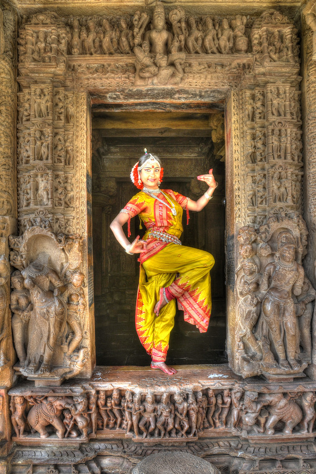 "Odissi dancer Bithika Mistry in a Odissi dance pose at the Khajuraho Temple.<br /> <br /> <br /> Khajuraho - Land Of The Moon God is located in the Indian state of Madhya Pradesh (MP) and roughly 620 kilometers (385 miles) southeast of New Delhi. Khajuraho was the cultural capital of the Chandela Rajputs, a Hindu dynasty that ruled from the 10th to 12th centuries. The temples of Khajuraho are famous for their so-called ""erotic sculptures"".<br /> <br /> Symbolising a medieval legacy, the Khajuraho temples are a perfect fusion of architectural and sculptural excellence, representing one of the finest examples of Indian art. To some, they are the most graphic, erotic and sensuous sculptures the world has ever known. But Khajuraho has not received the attention it deserves for its significant contribution to the religious art of India - there are literally hundreds of exquisite images on the interior and exterior walls of the shrines.<br /> <br /> Architecturally they are unique. While each temple has a distinct plan and design, several features are common to all. They are all built on high platforms, several metres off the ground. The stone used throughout is either granite or a combination of light sandstone and granite. Each of these temples has an entrance hall or mandapa, and a sanctum sanctorum or garbha griha. The roofs of these various sections have a distinct form. The porch and hall have pyramidal roofs made of several horizontal layers. The inner sanctum's roof is a conical tower - a colossal pile of stone (often 30m high) made of an arrangement of miniature towers called shikharas."