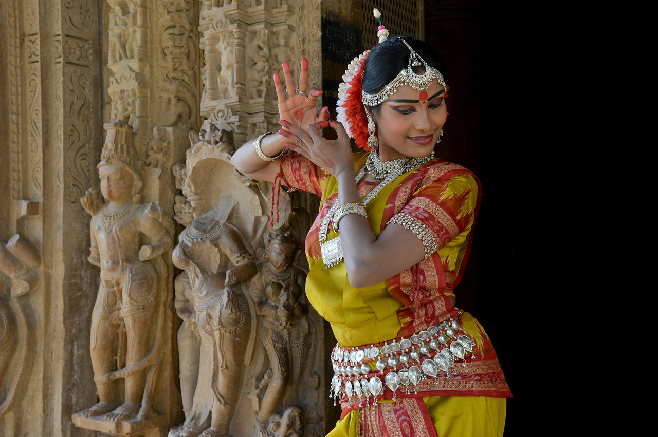 """Odissi dancer Bithika Mistry at the Khajuraho Temple in front of the stone carved statues.<br /> <br /> <br /> Khajuraho - Land Of The Moon God is located in the Indian state of Madhya Pradesh (MP) and roughly 620 kilometers (385 miles) southeast of New Delhi. Khajuraho was the cultural capital of the Chandela Rajputs, a Hindu dynasty that ruled from the 10th to 12th centuries. The temples of Khajuraho are famous for their so-called """"erotic sculptures"""".<br /> <br /> Symbolising a medieval legacy, the Khajuraho temples are a perfect fusion of architectural and sculptural excellence, representing one of the finest examples of Indian art. To some, they are the most graphic, erotic and sensuous sculptures the world has ever known. But Khajuraho has not received the attention it deserves for its significant contribution to the religious art of India - there are literally hundreds of exquisite images on the interior and exterior walls of the shrines.<br /> <br /> Architecturally they are unique. While each temple has a distinct plan and design, several features are common to all. They are all built on high platforms, several metres off the ground. The stone used throughout is either granite or a combination of light sandstone and granite. Each of these temples has an entrance hall or mandapa, and a sanctum sanctorum or garbha griha. The roofs of these various sections have a distinct form. The porch and hall have pyramidal roofs made of several horizontal layers. The inner sanctum's roof is a conical tower - a colossal pile of stone (often 30m high) made of an arrangement of miniature towers called shikharas."""