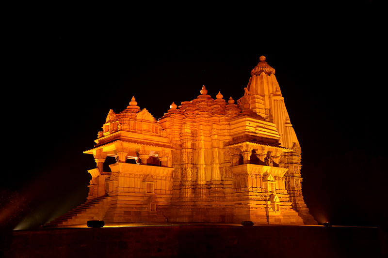 "Night view of the temple. Khajuraho - Land Of The Moon God is located in the Indian state of Madhya Pradesh (MP) and roughly 620 kilometers (385 miles) southeast of New Delhi. Khajuraho was the cultural capital of the Chandela Rajputs, a Hindu dynasty that ruled from the 10th to 12th centuries. The temples of Khajuraho are famous for their so-called ""erotic sculptures"".<br /> <br /> Symbolising a medieval legacy, the Khajuraho temples are a perfect fusion of architectural and sculptural excellence, representing one of the finest examples of Indian art. To some, they are the most graphic, erotic and sensuous sculptures the world has ever known. But Khajuraho has not received the attention it deserves for its significant contribution to the religious art of India - there are literally hundreds of exquisite images on the interior and exterior walls of the shrines.<br /> <br /> Architecturally they are unique. While each temple has a distinct plan and design, several features are common to all. They are all built on high platforms, several metres off the ground. The stone used throughout is either granite or a combination of light sandstone and granite. Each of these temples has an entrance hall or mandapa, and a sanctum sanctorum or garbha griha. The roofs of these various sections have a distinct form. The porch and hall have pyramidal roofs made of several horizontal layers. The inner sanctum's roof is a conical tower - a colossal pile of stone (often 30m high) made of an arrangement of miniature towers called shikharas."