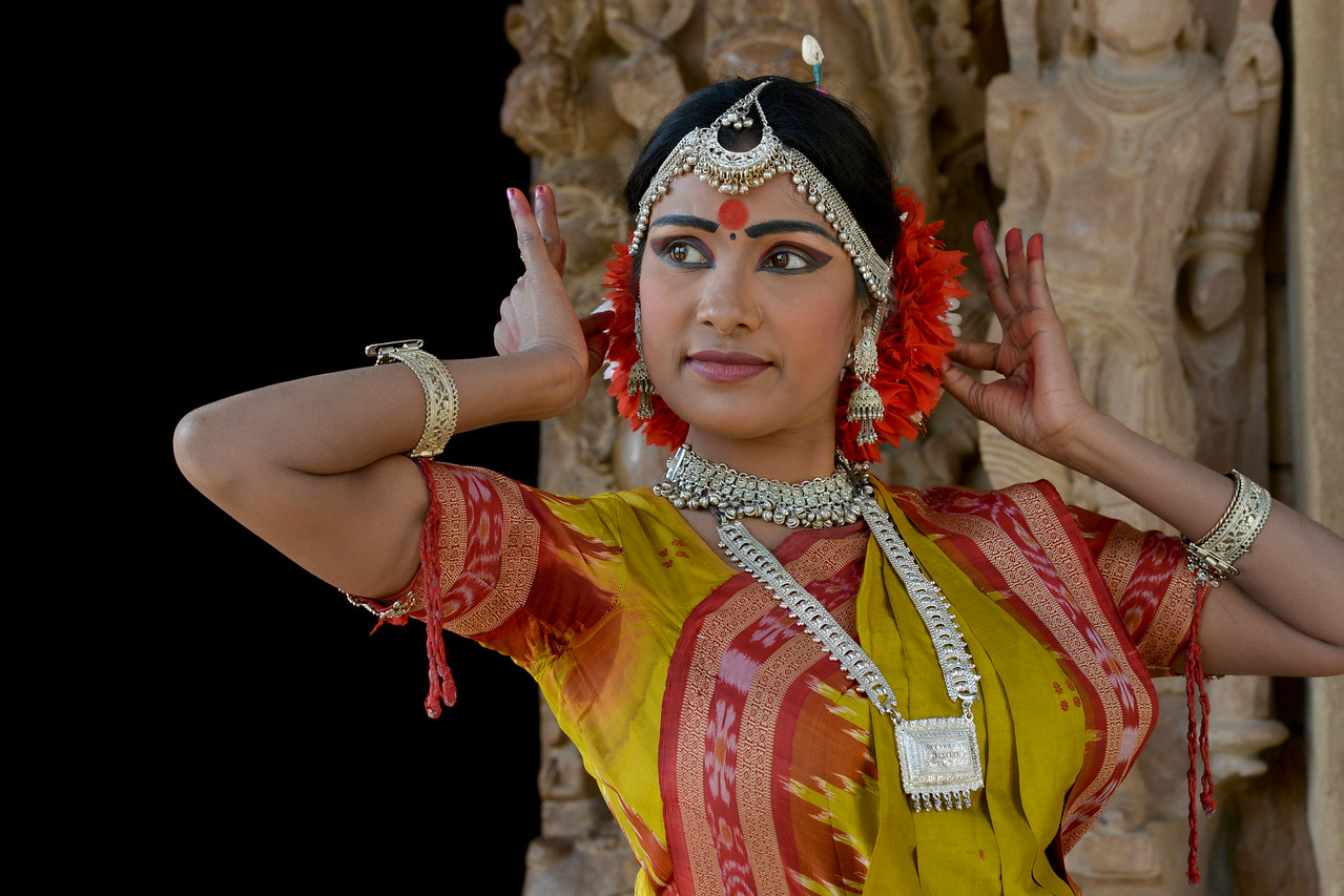 "Odissi dancer Bithika Mistry at the Khajuraho Temple strikes a dance pose.<br /> <br /> Khajuraho - Land Of The Moon God is located in the Indian state of Madhya Pradesh (MP) and roughly 620 kilometers (385 miles) southeast of New Delhi. Khajuraho was the cultural capital of the Chandela Rajputs, a Hindu dynasty that ruled from the 10th to 12th centuries. The temples of Khajuraho are famous for their so-called ""erotic sculptures"".<br /> <br /> Symbolising a medieval legacy, the Khajuraho temples are a perfect fusion of architectural and sculptural excellence, representing one of the finest examples of Indian art. To some, they are the most graphic, erotic and sensuous sculptures the world has ever known. But Khajuraho has not received the attention it deserves for its significant contribution to the religious art of India - there are literally hundreds of exquisite images on the interior and exterior walls of the shrines.<br /> <br /> Architecturally they are unique. While each temple has a distinct plan and design, several features are common to all. They are all built on high platforms, several metres off the ground. The stone used throughout is either granite or a combination of light sandstone and granite. Each of these temples has an entrance hall or mandapa, and a sanctum sanctorum or garbha griha. The roofs of these various sections have a distinct form. The porch and hall have pyramidal roofs made of several horizontal layers. The inner sanctum's roof is a conical tower - a colossal pile of stone (often 30m high) made of an arrangement of miniature towers called shikharas."