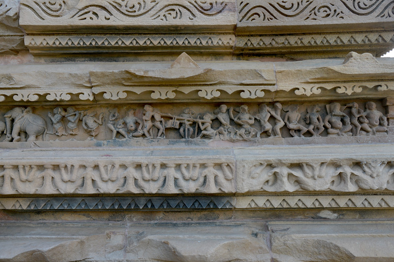 """Detailed and fine stone carvings at Khajuraho. Khajuraho - Land Of The Moon God is located in the Indian state of Madhya Pradesh (MP) and roughly 620 kilometers (385 miles) southeast of New Delhi. Khajuraho was the cultural capital of the Chandela Rajputs, a Hindu dynasty that ruled from the 10th to 12th centuries. The temples of Khajuraho are famous for their so-called """"erotic sculptures"""".<br /> <br /> Symbolising a medieval legacy, the Khajuraho temples are a perfect fusion of architectural and sculptural excellence, representing one of the finest examples of Indian art. To some, they are the most graphic, erotic and sensuous sculptures the world has ever known. But Khajuraho has not received the attention it deserves for its significant contribution to the religious art of India - there are literally hundreds of exquisite images on the interior and exterior walls of the shrines.<br /> <br /> Architecturally they are unique. While each temple has a distinct plan and design, several features are common to all. They are all built on high platforms, several metres off the ground. The stone used throughout is either granite or a combination of light sandstone and granite. Each of these temples has an entrance hall or mandapa, and a sanctum sanctorum or garbha griha. The roofs of these various sections have a distinct form. The porch and hall have pyramidal roofs made of several horizontal layers. The inner sanctum's roof is a conical tower - a colossal pile of stone (often 30m high) made of an arrangement of miniature towers called shikharas."""