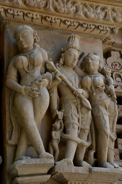 """Close up details of the temple carvings. Khajuraho - Land Of The Moon God is located in the Indian state of Madhya Pradesh (MP) and roughly 620 kilometers (385 miles) southeast of New Delhi. Khajuraho was the cultural capital of the Chandela Rajputs, a Hindu dynasty that ruled from the 10th to 12th centuries. The temples of Khajuraho are famous for their so-called """"erotic sculptures"""".<br /> <br /> Symbolising a medieval legacy, the Khajuraho temples are a perfect fusion of architectural and sculptural excellence, representing one of the finest examples of Indian art. To some, they are the most graphic, erotic and sensuous sculptures the world has ever known. But Khajuraho has not received the attention it deserves for its significant contribution to the religious art of India - there are literally hundreds of exquisite images on the interior and exterior walls of the shrines.<br /> <br /> Architecturally they are unique. While each temple has a distinct plan and design, several features are common to all. They are all built on high platforms, several metres off the ground. The stone used throughout is either granite or a combination of light sandstone and granite. Each of these temples has an entrance hall or mandapa, and a sanctum sanctorum or garbha griha. The roofs of these various sections have a distinct form. The porch and hall have pyramidal roofs made of several horizontal layers. The inner sanctum's roof is a conical tower - a colossal pile of stone (often 30m high) made of an arrangement of miniature towers called shikharas."""