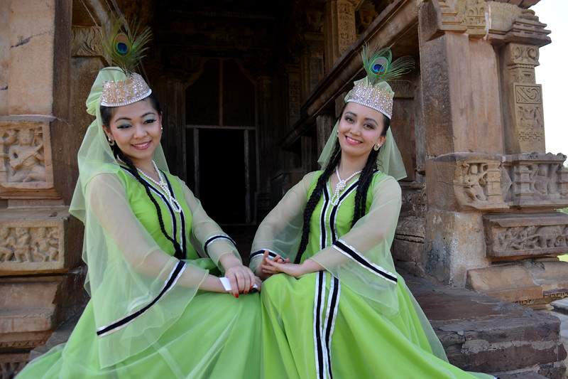 "Two Uzbek dancers from Uzbekistan at the Khajuraho Temple. <br /> Khajuraho - Land Of The Moon God is located in the Indian state of Madhya Pradesh (MP) and roughly 620 kilometers (385 miles) southeast of New Delhi. Khajuraho was the cultural capital of the Chandela Rajputs, a Hindu dynasty that ruled from the 10th to 12th centuries. The temples of Khajuraho are famous for their so-called ""erotic sculptures"".<br /> <br /> Symbolising a medieval legacy, the Khajuraho temples are a perfect fusion of architectural and sculptural excellence, representing one of the finest examples of Indian art. To some, they are the most graphic, erotic and sensuous sculptures the world has ever known. But Khajuraho has not received the attention it deserves for its significant contribution to the religious art of India - there are literally hundreds of exquisite images on the interior and exterior walls of the shrines.<br /> <br /> Architecturally they are unique. While each temple has a distinct plan and design, several features are common to all. They are all built on high platforms, several metres off the ground. The stone used throughout is either granite or a combination of light sandstone and granite. Each of these temples has an entrance hall or mandapa, and a sanctum sanctorum or garbha griha. The roofs of these various sections have a distinct form. The porch and hall have pyramidal roofs made of several horizontal layers. The inner sanctum's roof is a conical tower - a colossal pile of stone (often 30m high) made of an arrangement of miniature towers called shikharas."