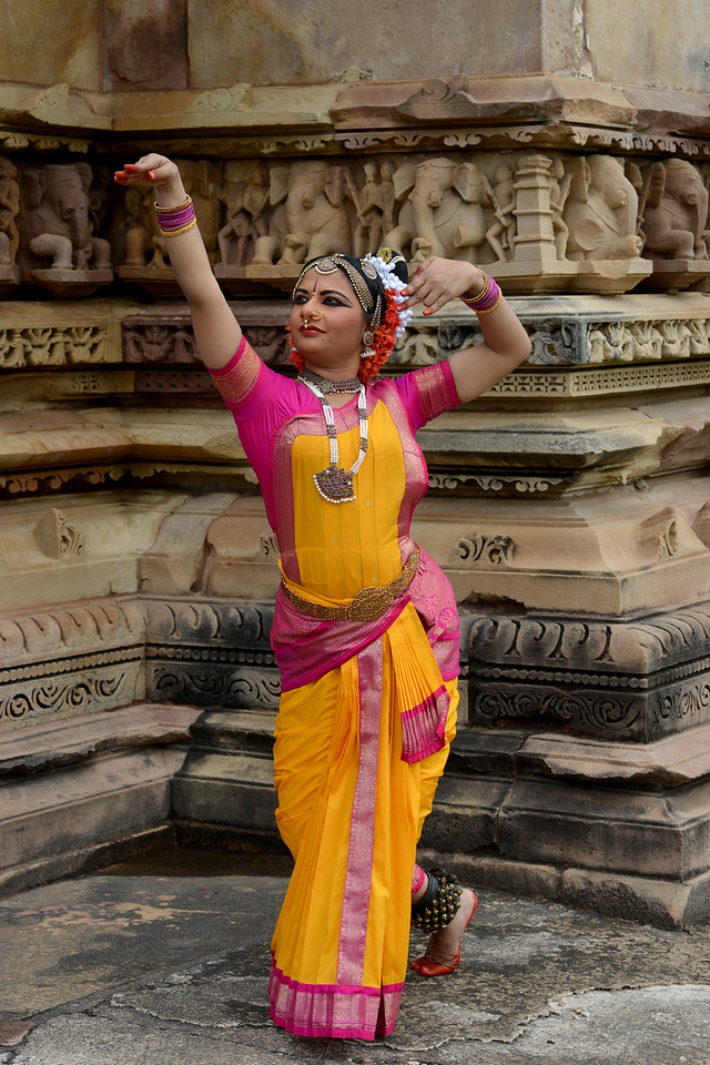 "Kuchipudi dancer Abhinaya Nagajothy striking a dance pose at the Khajuraho Temple. <br /> Khajuraho - Land Of The Moon God is located in the Indian state of Madhya Pradesh (MP) and roughly 620 kilometers (385 miles) southeast of New Delhi. Khajuraho was the cultural capital of the Chandela Rajputs, a Hindu dynasty that ruled from the 10th to 12th centuries. The temples of Khajuraho are famous for their so-called ""erotic sculptures"".<br /> <br /> Symbolising a medieval legacy, the Khajuraho temples are a perfect fusion of architectural and sculptural excellence, representing one of the finest examples of Indian art. To some, they are the most graphic, erotic and sensuous sculptures the world has ever known. But Khajuraho has not received the attention it deserves for its significant contribution to the religious art of India - there are literally hundreds of exquisite images on the interior and exterior walls of the shrines.<br /> <br /> Architecturally they are unique. While each temple has a distinct plan and design, several features are common to all. They are all built on high platforms, several metres off the ground. The stone used throughout is either granite or a combination of light sandstone and granite. Each of these temples has an entrance hall or mandapa, and a sanctum sanctorum or garbha griha. The roofs of these various sections have a distinct form. The porch and hall have pyramidal roofs made of several horizontal layers. The inner sanctum's roof is a conical tower - a colossal pile of stone (often 30m high) made of an arrangement of miniature towers called shikharas."