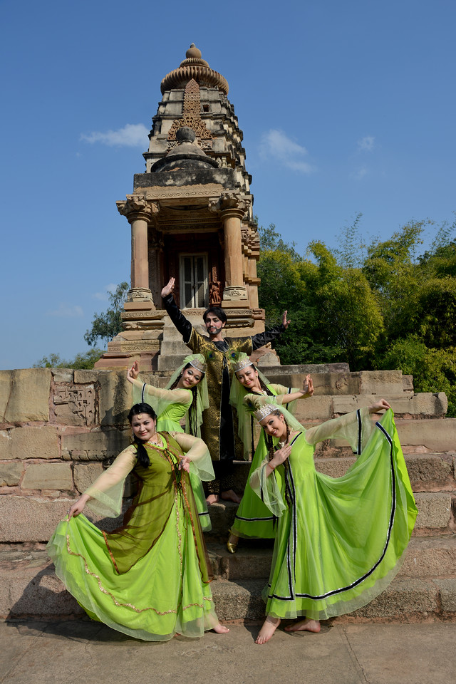 "Two Uzbek-dancers from Uzbekistan strike a pose at the Khajuraho Temple. <br /> Khajuraho - Land Of The Moon God is located in the Indian state of Madhya Pradesh (MP) and roughly 620 kilometers (385 miles) southeast of New Delhi. Khajuraho was the cultural capital of the Chandela Rajputs, a Hindu dynasty that ruled from the 10th to 12th centuries. The temples of Khajuraho are famous for their so-called ""erotic sculptures"".<br /> <br /> Symbolising a medieval legacy, the Khajuraho temples are a perfect fusion of architectural and sculptural excellence, representing one of the finest examples of Indian art. To some, they are the most graphic, erotic and sensuous sculptures the world has ever known. But Khajuraho has not received the attention it deserves for its significant contribution to the religious art of India - there are literally hundreds of exquisite images on the interior and exterior walls of the shrines.<br /> <br /> Architecturally they are unique. While each temple has a distinct plan and design, several features are common to all. They are all built on high platforms, several metres off the ground. The stone used throughout is either granite or a combination of light sandstone and granite. Each of these temples has an entrance hall or mandapa, and a sanctum sanctorum or garbha griha. The roofs of these various sections have a distinct form. The porch and hall have pyramidal roofs made of several horizontal layers. The inner sanctum's roof is a conical tower - a colossal pile of stone (often 30m high) made of an arrangement of miniature towers called shikharas."